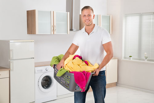 Man Carrying Laundry Basket In Kitchen Room